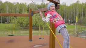 Ευτυχής το κορίτσι που έχει τη διασκέδαση στην ταλάντευση στην παιδική χαρά απόθεμα βίντεο