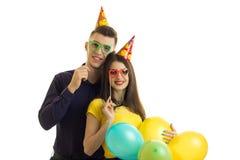 Ευτυχής τύπος με ένα κορίτσι στα χρωματισμένα γυαλιά που φέρνουν τα πολύχρωμα μπαλόνια Στοκ φωτογραφία με δικαίωμα ελεύθερης χρήσης