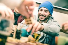 Ευτυχής τύπος με τους φίλους που τρώνε τα τρόφιμα δάχτυλων και που πίνουν την μπύρα Στοκ Εικόνες