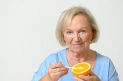 Ευτυχής υγιής ανώτερη κυρία με ένα πορτοκάλι Στοκ εικόνα με δικαίωμα ελεύθερης χρήσης