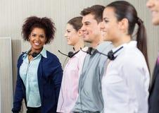 Ευτυχής υπάλληλος τηλεφωνικών κέντρων θηλυκών που στέκεται με Στοκ Εικόνες