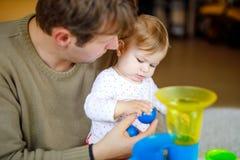 Ευτυχής υπερήφανος νέος πατέρας που έχει τη διασκέδαση με την κόρη μωρών, οικογενειακό πορτρέτο από κοινού Παιχνίδι μπαμπάδων με  στοκ φωτογραφίες