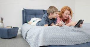 Ευτυχής υπολογιστής ταμπλετών λαβής μητέρων και γιων που βρίσκεται στο κρεβάτι στην κρεβατοκάμαρα, χρόνος οικογενειακών εξόδων απ απόθεμα βίντεο
