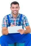 Ευτυχής υδραυλικός που γράφει στην περιοχή αποκομμάτων καθμένος στην εργαλειοθήκη Στοκ Εικόνες