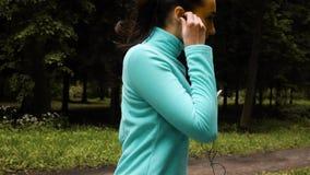 Ευτυχής φίλαθλη γυναίκα στα ακουστικά υπαίθρια στο πάρκο φιλμ μικρού μήκους