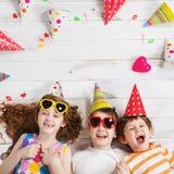 Ευτυχής φίλος παιδιών που βρίσκεται σε ένα ξύλινο πάτωμα στο κόμμα καρναβαλιού Στοκ φωτογραφίες με δικαίωμα ελεύθερης χρήσης