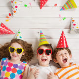 Ευτυχής φίλος παιδιών στο κόμμα καρναβαλιού, που βρίσκεται σε ένα ξύλινο πάτωμα στοκ φωτογραφίες με δικαίωμα ελεύθερης χρήσης
