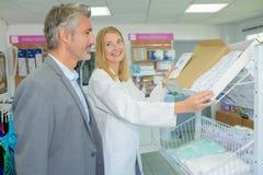Ευτυχής φαρμακοποιός που βοηθά τον αρσενικό πελάτη στο φαρμακείο στοκ εικόνες με δικαίωμα ελεύθερης χρήσης