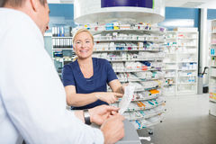Ευτυχής φαρμακοποιός που εξηγεί τις λεπτομέρειες του προϊόντος στοκ εικόνες