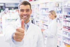 Ευτυχής φαρμακοποιός που κρατά τον αντίχειρά του στοκ φωτογραφία