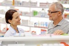 Ευτυχής φαρμακοποιός που μιλά στο ανώτερο άτομο στο φαρμακείο στοκ φωτογραφία