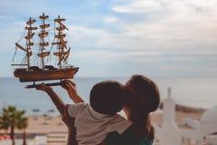 Ευτυχής φιλώντας μητέρα αγοριών και κράτημα του προτύπου σκαφών επάνω Στοκ Φωτογραφία