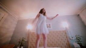 Ευτυχής φρέσκια γυναίκα brunette στο φόρεμα νύχτας που πηδά στο κρεβάτι, που έχει τη διασκέδαση Όμορφο κορίτσι που αισθάνεται ευτ απόθεμα βίντεο