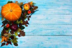 Ευτυχής χαιρετισμός ημέρας των ευχαριστιών με τα φύλλα πτώσης στην μπλε ξύλινη ΤΣΕ στοκ εικόνες με δικαίωμα ελεύθερης χρήσης