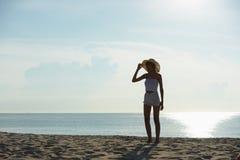 Ευτυχής χαλάρωση ζευγών στην παραλία στην ανατολή, πίσω άποψη Στοκ Φωτογραφίες