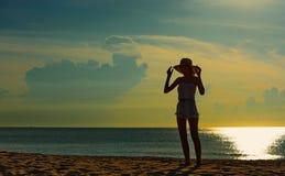 Ευτυχής χαλάρωση ζευγών στην παραλία στην ανατολή, πίσω άποψη Στοκ Εικόνα