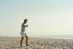 Ευτυχής χαλάρωση ζευγών στην παραλία στην ανατολή, πίσω άποψη Στοκ εικόνα με δικαίωμα ελεύθερης χρήσης