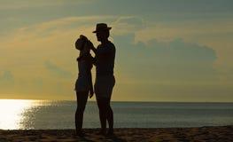 Ευτυχής χαλάρωση ζευγών στην παραλία στην ανατολή, πίσω άποψη Στοκ εικόνες με δικαίωμα ελεύθερης χρήσης