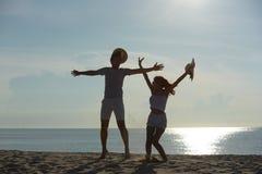 Ευτυχής χαλάρωση ζευγών στην παραλία στην ανατολή, πίσω άποψη Στοκ φωτογραφία με δικαίωμα ελεύθερης χρήσης