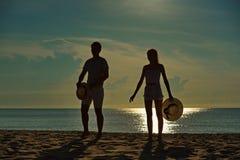 Ευτυχής χαλάρωση ζευγών στην παραλία στην ανατολή, πίσω άποψη Στοκ Εικόνες