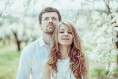 Ευτυχής χαλάρωση ζεύγους χαμόγελου στον ανθίζοντας κήπο δέντρων μηλιάς ανατρέχοντας άτομο Οριζόντιος πυροβολισμός πορτρέτου Στοκ Φωτογραφία