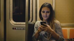 Ευτυχής χαλαρωμένη όμορφη χιλιετής συνεδρίαση κοριτσιών στα βίντεο προσοχής τραίνων μετρό on-line στο smartphone app και χαμόγελο φιλμ μικρού μήκους