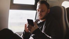 Ευτυχής χαλαρωμένος ευρωπαϊκός ανεξάρτητος εργαζόμενος που χρησιμοποιεί τον αγγελιοφόρο app smartphone που απολαμβάνει το άνετο τ απόθεμα βίντεο