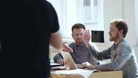 Ευτυχής χαλαρωμένος νέος αρσενικός κύριος επιχειρηματίας που μιλά στους χαμογελώντας συναδέλφους στο σύγχρονο πίνακα εργασιακών χ απόθεμα βίντεο