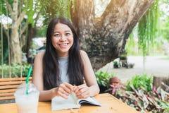 Ευτυχής χαλαρώστε τους χρόνους με το βιβλίο ανάγνωσης, ασιατικό χαμόγελο εφήβων γυναικών ταϊλανδικό με το βιβλίο στον κήπο Στοκ φωτογραφία με δικαίωμα ελεύθερης χρήσης
