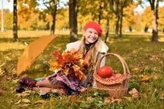 ευτυχής χαμογελώντας έφ&e Πορτρέτο φθινοπώρου του όμορφου νέου κοριτσιού στο κόκκινο καπέλο στοκ εικόνα
