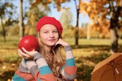 ευτυχής χαμογελώντας έφ&e Πορτρέτο φθινοπώρου του όμορφου νέου κοριτσιού στο κόκκινο καπέλο στοκ εικόνες