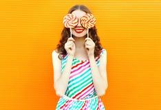 Ευτυχής χαμογελώντας γυναίκα πορτρέτου που κρύβει τα μάτια της με το lollipop δύο στο ζωηρόχρωμο ριγωτό φόρεμα στον πορτοκαλή τοί στοκ φωτογραφίες