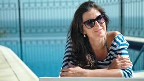 Ευτυχής χαμογελώντας γυναίκα πορτρέτου στα γυαλιά ηλίου που απολαμβάνει τις διακοπές που βρίσκονται στην καρέκλα γεφυρών με τα όπ απόθεμα βίντεο