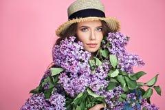 Ευτυχής χαμογελώντας γυναίκα που απολαμβάνει τη μυρωδιά των ιωδών λουλουδιών ανθοδεσμών πέρα από το ζωηρόχρωμο μπλε υπόβαθρο στοκ φωτογραφία με δικαίωμα ελεύθερης χρήσης