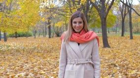 Ευτυχής χαμογελώντας γυναίκα που περπατά στο πάρκο φθινοπώρου με το κίτρινο φύλλωμα απόθεμα βίντεο