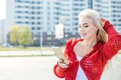 Ευτυχής χαμογελώντας γυναίκα που φορά ένα κόκκινο πουλόβερ που κρατά ένα τηλέφωνο κυττάρων Στοκ Εικόνα
