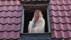 Ευτυχής χαμογελώντας γυναίκα στο παράθυρο που εξετάζει τη κάμερα και που στέλνει στο σπίτι ένα φιλί απόθεμα βίντεο
