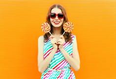 Ευτυχής χαμογελώντας εκμετάλλευση γυναικών lollipop στα κόκκινα διαμορφωμένα καρδιά γυαλιά ηλίου, ζωηρόχρωμο ριγωτό φόρεμα στον π στοκ φωτογραφίες