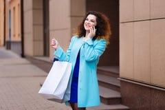 Ευτυχής χαμογελώντας ελκυστική νέα γυναίκα με την ομιλία τσαντών αγορών Στοκ Φωτογραφία