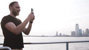 Ευτυχής χαμογελώντας ευρωπαϊκός αρσενικός ταξιδιώτης που κάνει μια τηλεοπτική κλήση που χρησιμοποιεί το smartphone σε ένα ταξίδι  φιλμ μικρού μήκους