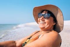 Ευτυχής χαμογελώντας ηλικιωμένη γυναίκα womanr στα γυαλιά ηλίου και το μεγάλο καπέλο tak στοκ εικόνες