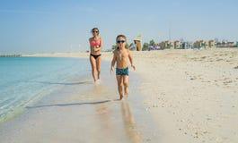 Ευτυχής χαμογελώντας μητέρα και ο γιος της που παίζουν και που τρέχουν στην παραλία Έννοια της φιλικής οικογένειας Στοκ Εικόνες