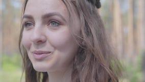 Ευτυχής χαμογελώντας νέα γυναίκα πορτρέτου κινηματογραφήσεων σε πρώτο πλάνο που κοιτάζει γύρω και κεκλεισμένων των θυρών που στέκ φιλμ μικρού μήκους