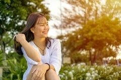 Ευτυχής χαμογελώντας νέα γυναίκα που κάθεται και που κτυπά την τρίχα της στοκ φωτογραφία με δικαίωμα ελεύθερης χρήσης