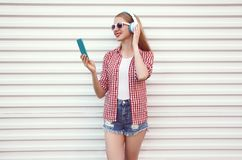 Ευτυχής χαμογελώντας νέα γυναίκα στα ακουστικά με το smartphone που ακούει τη μουσική που φορά το ελεγμένο πουκάμισο, σορτς στο λ στοκ εικόνα με δικαίωμα ελεύθερης χρήσης