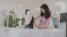Ευτυχής χαμογελώντας νέα γυναίκα brunette που εργάζεται στο ατελιέ της Είναι σχεδιαστής υφασμάτων και δημιουργεί τις μοντέρνες θη απόθεμα βίντεο
