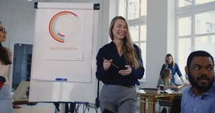 Ευτυχής χαμογελώντας ξανθή επιχειρησιακή γυναίκα που δίνει το κίνητρο στη νέα multiethnic ομάδα συναδέλφων στη σύγχρονη συνεδρίασ φιλμ μικρού μήκους
