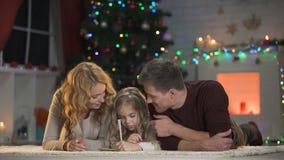 Ευτυχής χαμογελώντας οικογένεια που συνθέτει την επιστολή για Santa, πεποίθηση στο παραμύθι Χριστουγέννων απόθεμα βίντεο