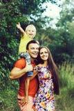 Ευτυχής χαμογελώντας οικογένεια στο πράσινο θερινό πάρκο στοκ εικόνες