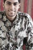 Ευτυχής χαμογελώντας αραβικός αιγυπτιακός νεαρός άνδρας στο στρατιωτικό κοστούμι Στοκ Φωτογραφία